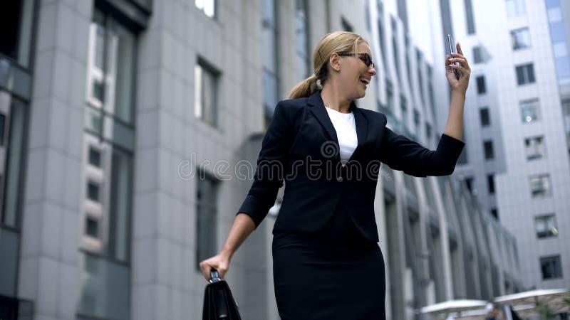 疯狂的女商人满意对智能手机,关于促进的消息在事业 免版税库存照片