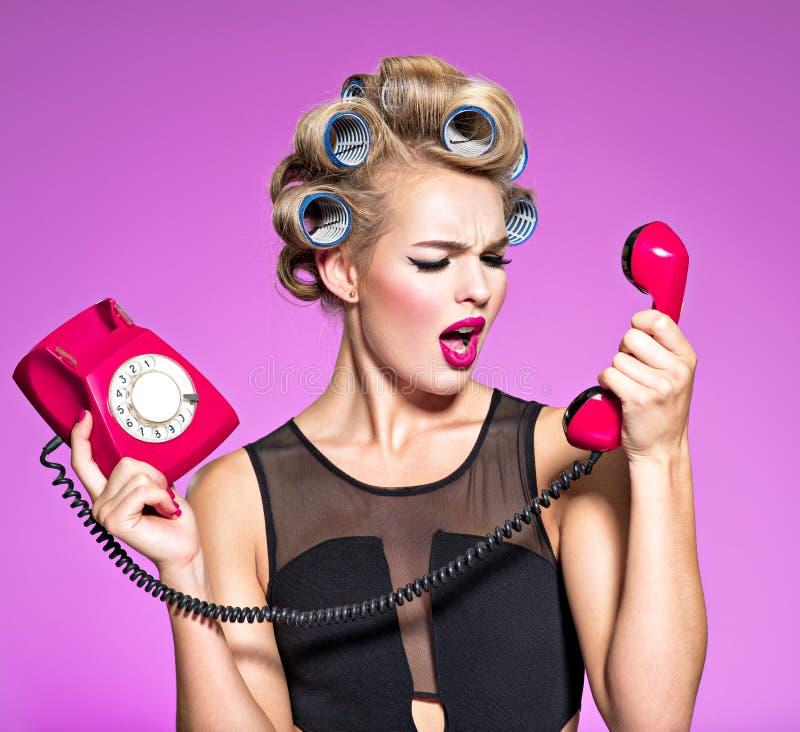 疯狂的恼怒的白种人妇女叫喊对减速火箭的电话 免版税库存图片