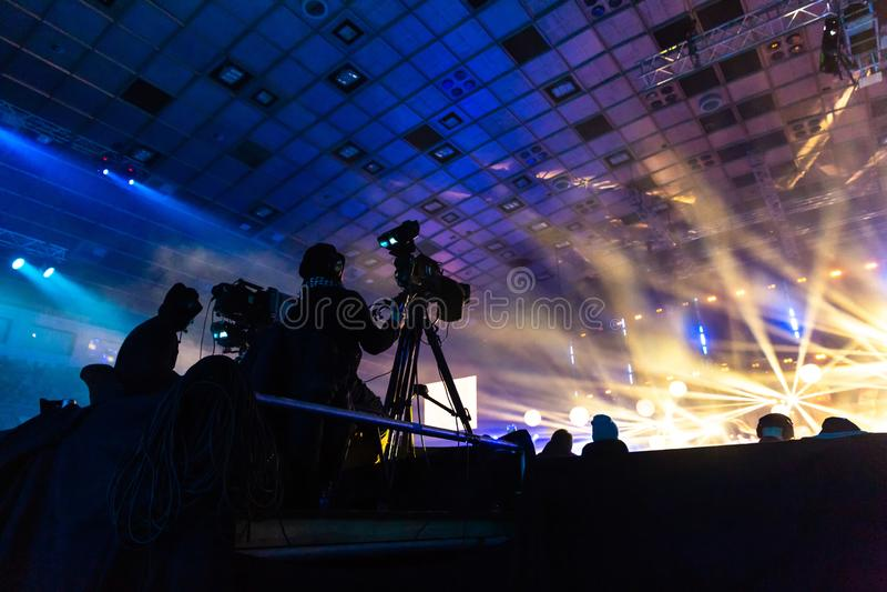 由一位摄影师的电视广播在音乐会期间 与操作员的照相机在高平台 库存照片