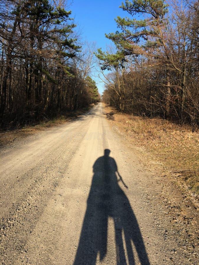由后照的骑自行车者的阴影沿土山路舒展 库存图片