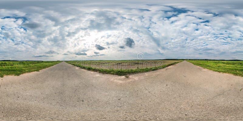 由180度的充分的无缝的球状全景360在石渣路的角度图在与令人敬畏的云彩的领域中在equirectangular 免版税库存照片
