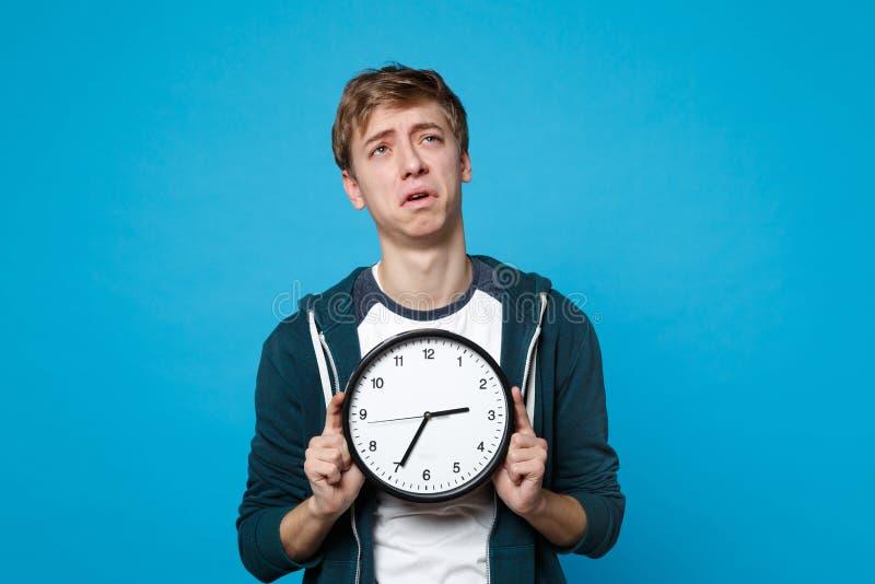 疲乏的哭泣的年轻人画象拿着圆的时钟的便服的被隔绝在蓝色墙壁背景在演播室 免版税库存图片