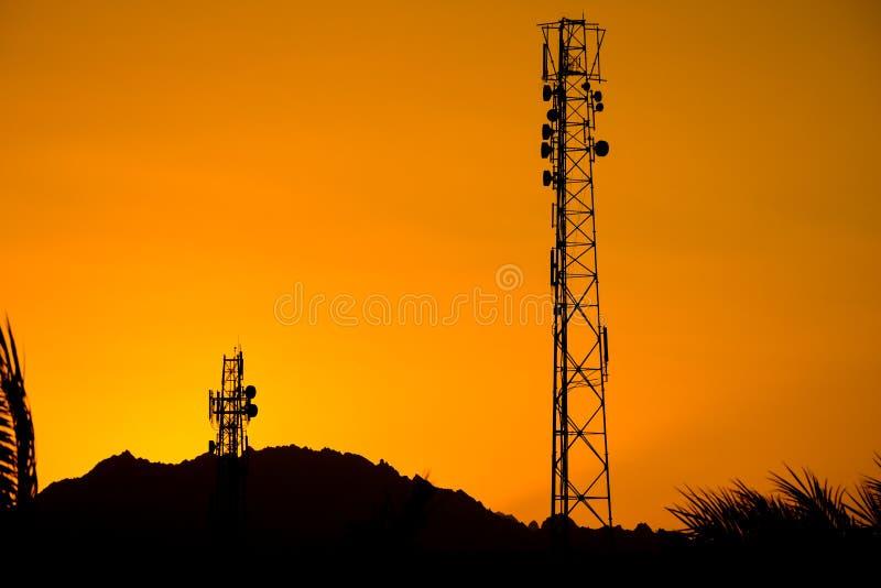 电信天线多孔的塔剪影电话的与美好的日落 免版税库存照片