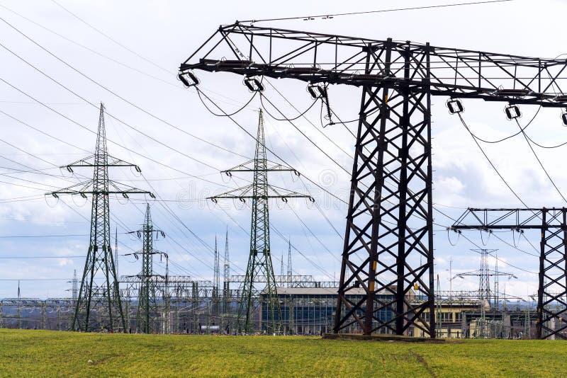 电定向塔举办当前从发行与剧烈的多云天空拷贝空间的发电站 免版税库存照片