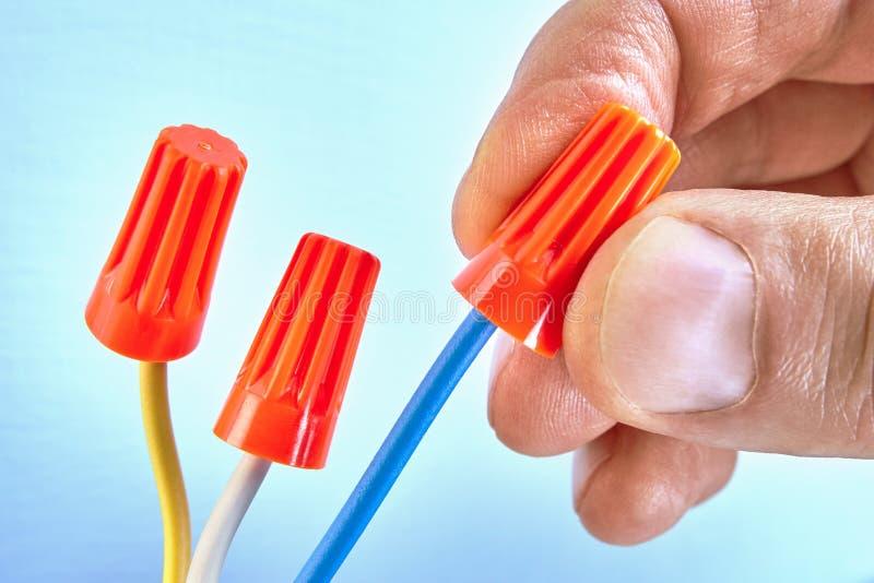 电工拿着在导线的导线连接器 免版税库存照片