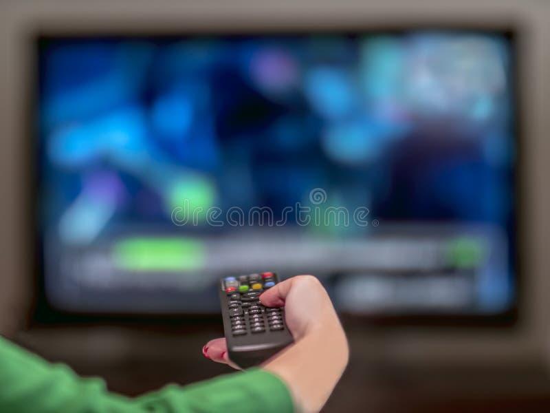 电视遥远在一名妇女的手上有红色修指甲的 库存照片