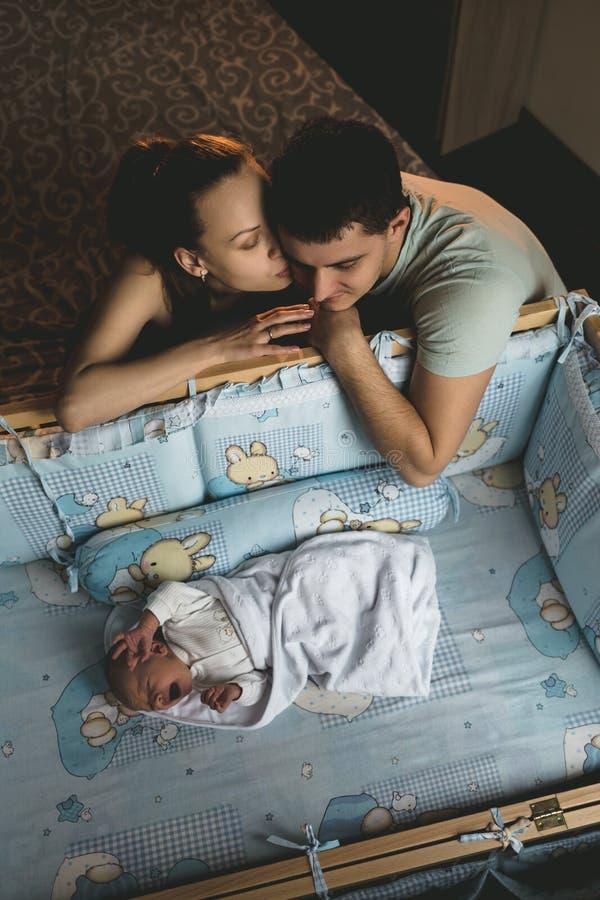 男人和一名妇女在他们新出生附近 父母亲吻 在他的小儿床的男孩哭喊 小爸爸妈妈 年轻家庭画象 家庭生活 库存图片