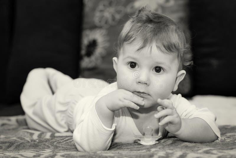 男婴在肚子说谎 男婴摆在并且使用与安慰者 免版税库存照片