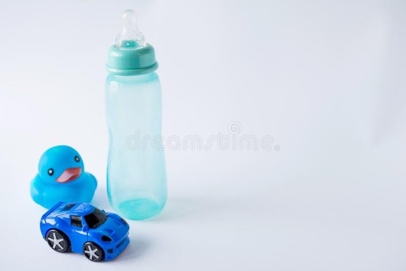 男婴辅助部件背景:瓶、蓝色鸭子和汽车在白色背景与拷贝空间;顶视图 初期的概念 免版税图库摄影