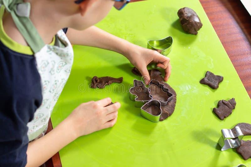 男孩从在滚动的棕色面团的模子紧压形状 被按的形状是在旁边为烘烤做准备 免版税库存图片