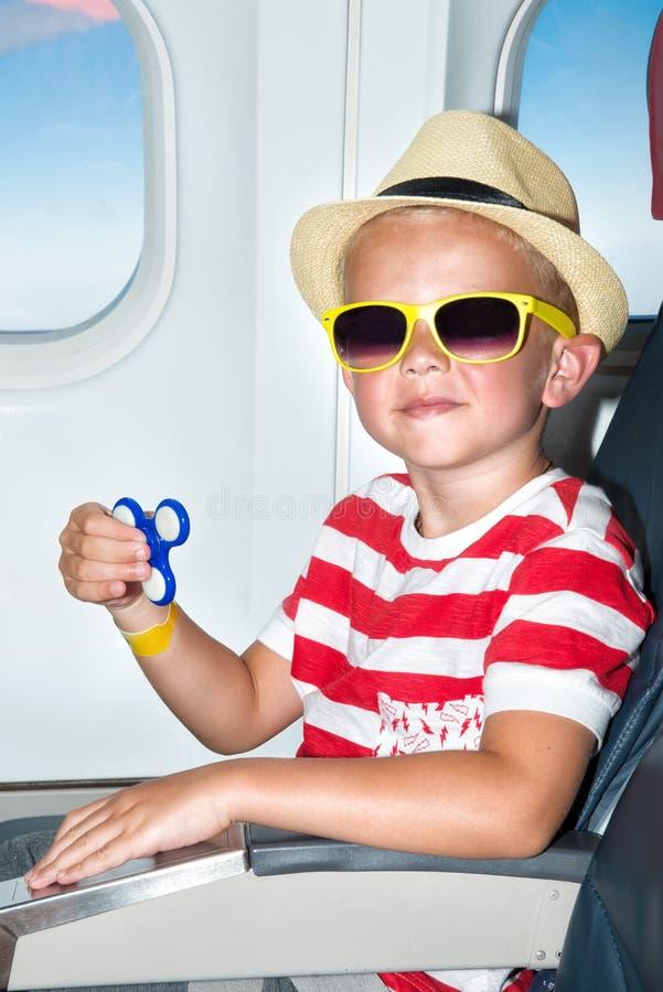 男孩使用与在飞机上的锭床工人 花梢玩具 库存照片