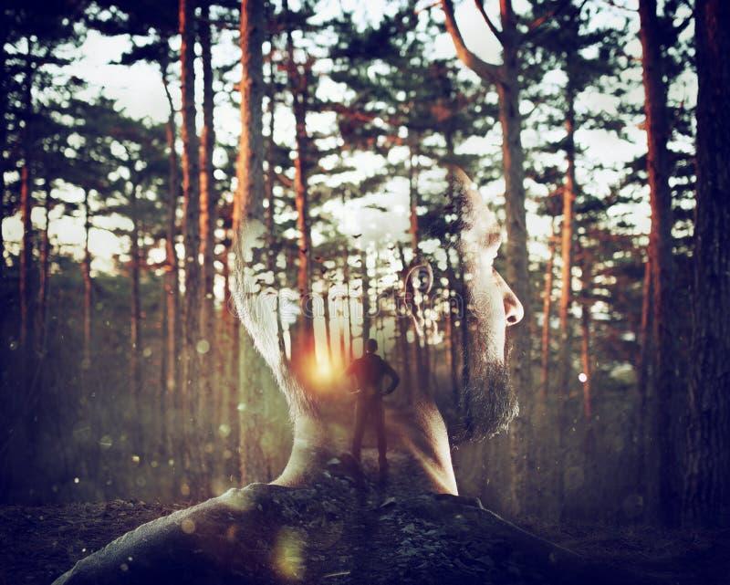 男孩想着他自己在森林两次曝光的 免版税图库摄影