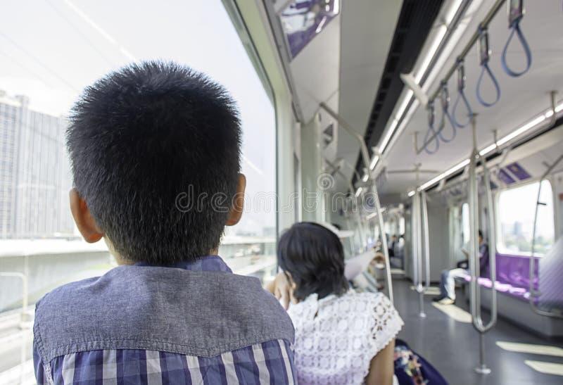 男孩看风景火车窗口外在城市 免版税库存照片