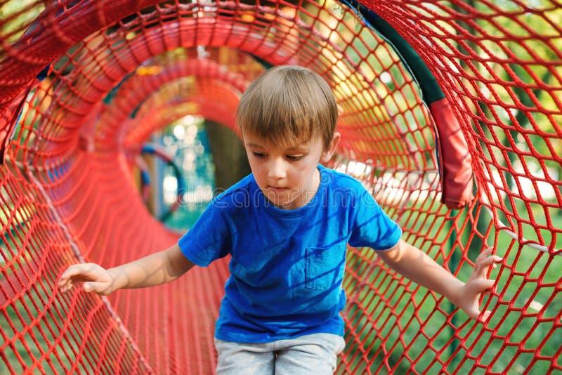 男孩逗人喜爱少许户外使用 孩子获得乐趣在隧道在现代操场 愉快的童年 您系列节日快乐的夏天 库存图片
