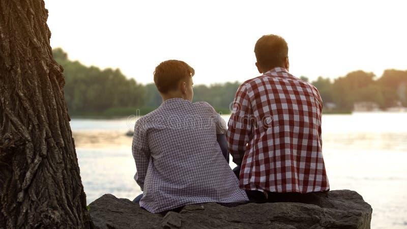 男性坐石头在湖附近和谈论生活的少年和他的父亲 免版税库存照片