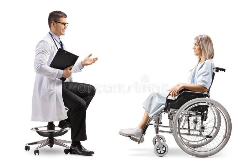 男性医生坐和谈话与轮椅的一名年轻女性患者 免版税库存照片