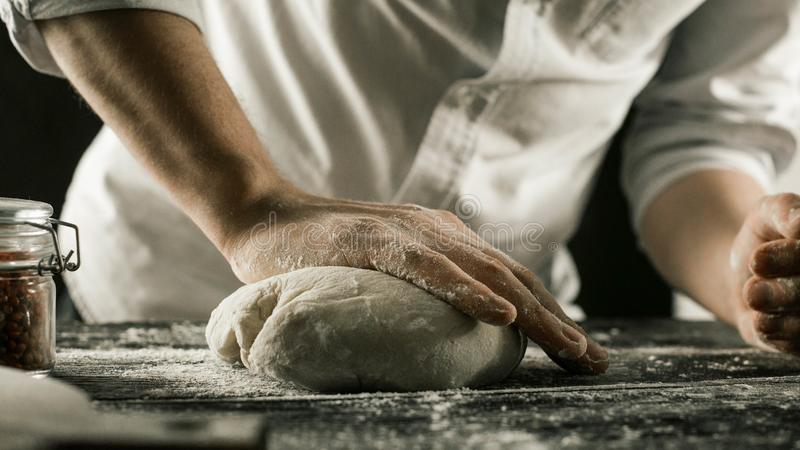 男性厨师手揉面团用在厨房用桌上的面粉 免版税库存图片