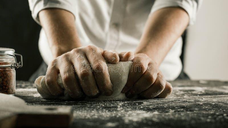 男性厨师手揉面团用在厨房用桌上的面粉 库存照片