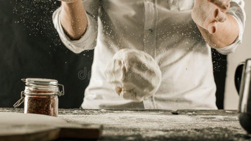 男性厨师手揉面团用在厨房用桌上的面粉 免版税库存照片