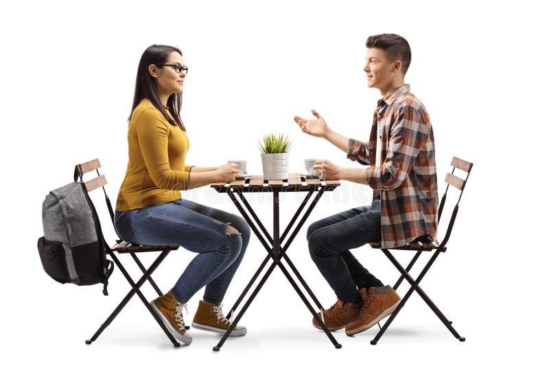 男性和女生食用咖啡和谈话在咖啡馆 免版税图库摄影