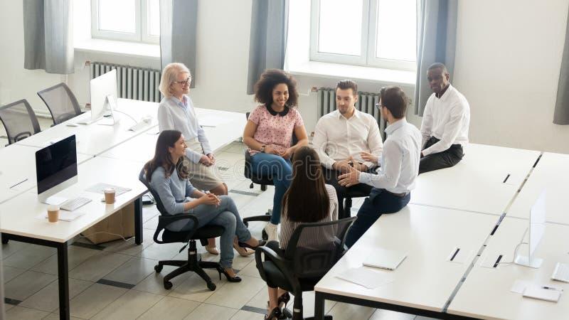 男性教练辅导者讲话在公司小组聚会,顶视图上 免版税库存照片