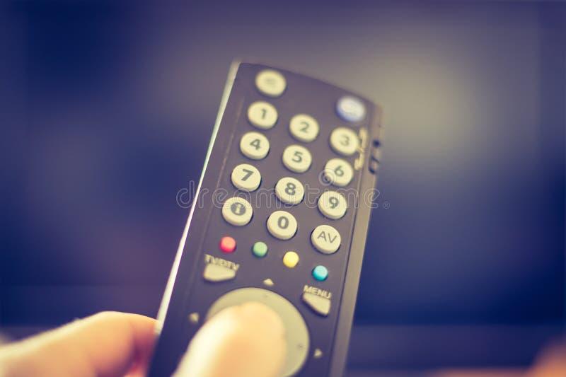 男性手拿着电视遥控,聪明的电视 免版税图库摄影