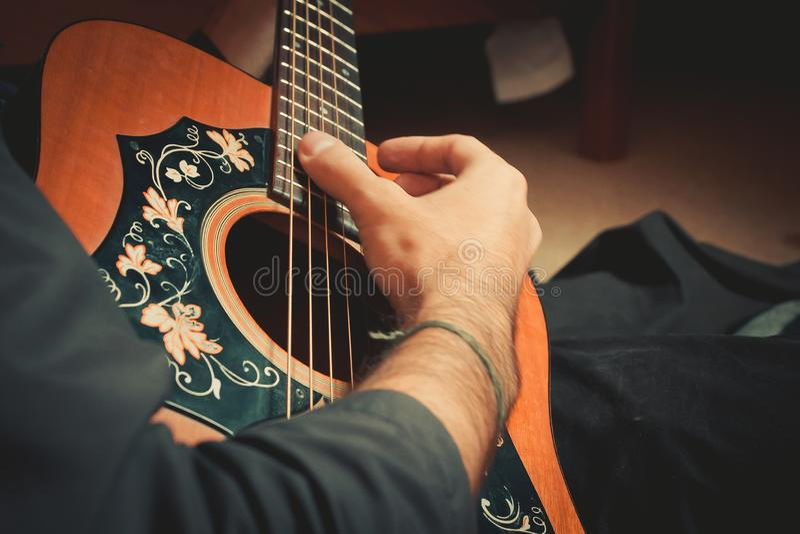 男性手播放老吉他特写镜头的串 免版税库存照片
