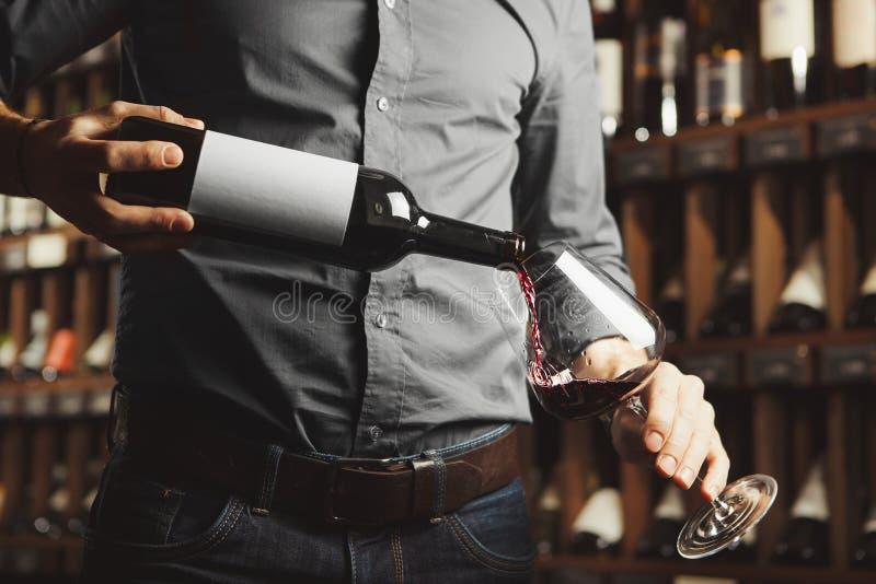 男性斟酒服务员倾吐的红酒接近的照片到葡萄酒杯里 有瓶的侍者酒精饮料 图库摄影