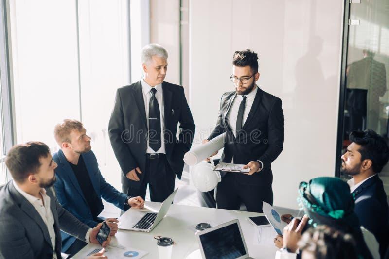 男性经理做flipchart介绍给不同的同事在见面 图库摄影