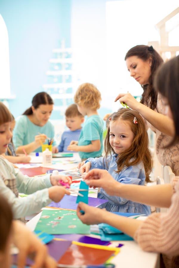 画与铅笔和胶合用在艺术课的胶浆棍子的小组学龄前孩子在幼儿园或托儿所 库存照片