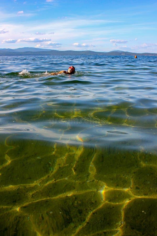 画在湖的底部用清楚的水 很远活跃妇女浮游物 免版税库存图片