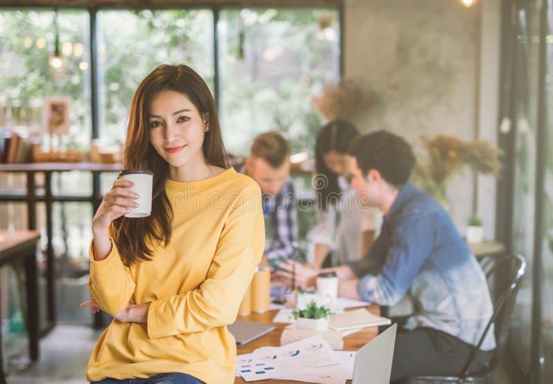 画象亚洲女性创造性运作的队coworking的办公室,拿着咖啡杯的微笑愉快的美女手 免版税库存图片