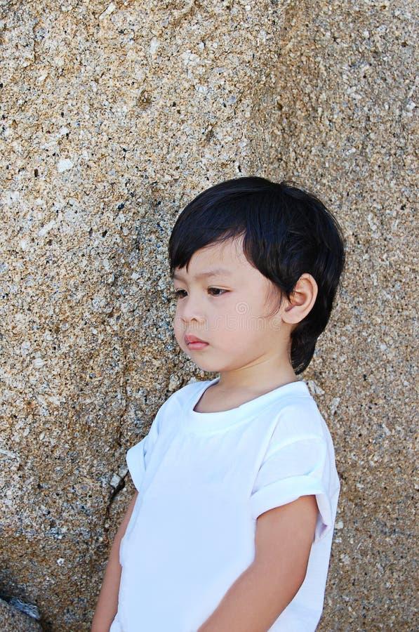 画象亚裔男孩在泰国微笑着背景石头,在Satun的酸值Lipe 免版税库存图片