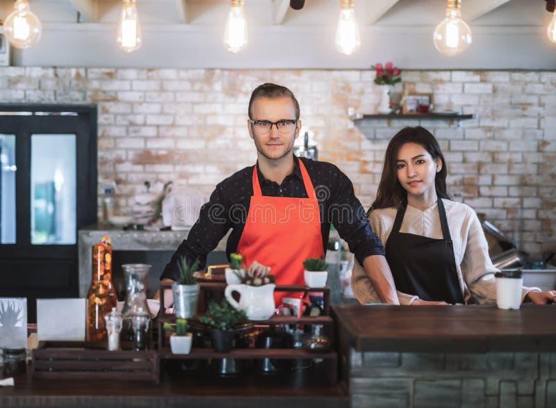 画象企业主夫妇穿戴围裙 免版税库存照片