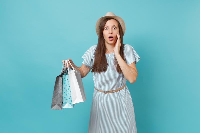 画象相当冲击了夏天礼服的,拿着与购买的草帽哀伤的美丽的白种人妇女包裹袋子 库存图片