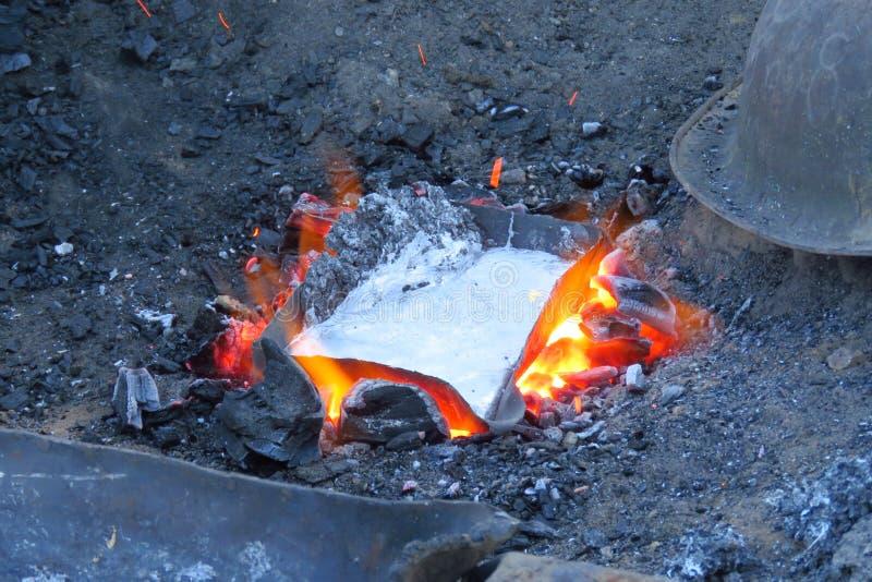 生产煎锅的熔化的金属罐头,数字,尼泊尔 免版税图库摄影