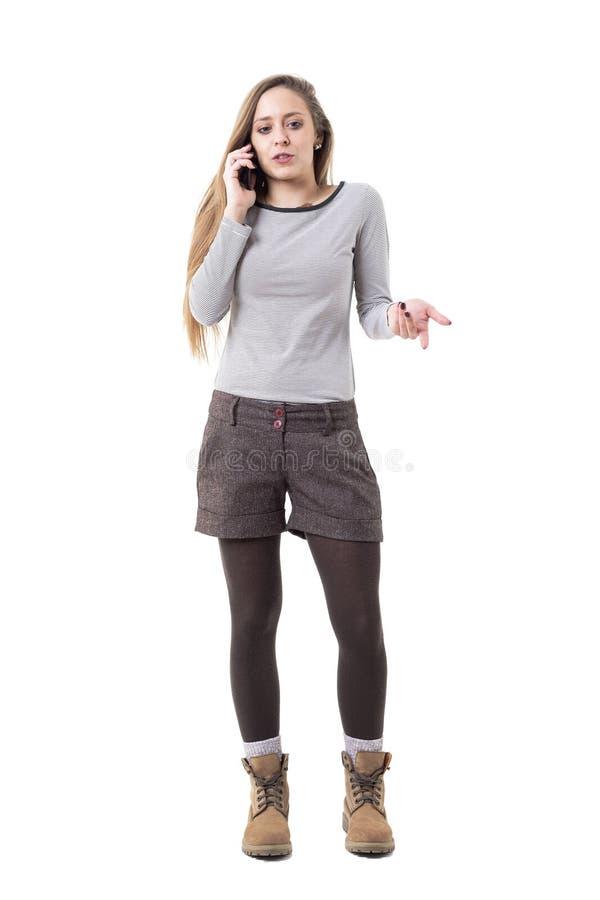 生气年轻时髦的妇女争论在看的电话姿势示意和下来 免版税库存图片
