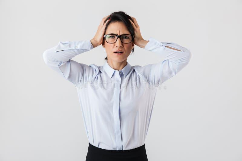 生气站立在办公室的秘书妇女佩带的镜片的图象,被隔绝在白色背景 免版税库存照片