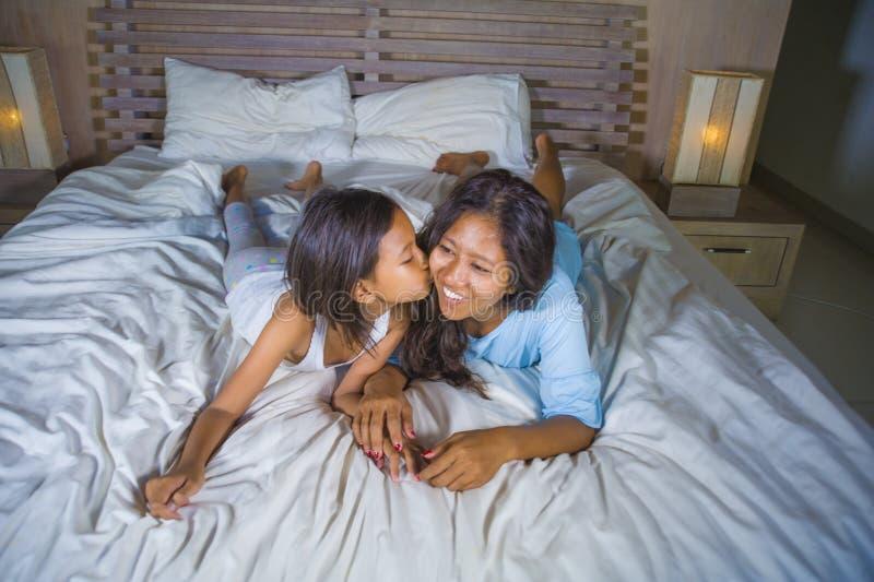 生活方式在家摆在与她美好的8岁的愉快的亚裔妇女卧室画象床微笑的女儿嬉戏 库存照片
