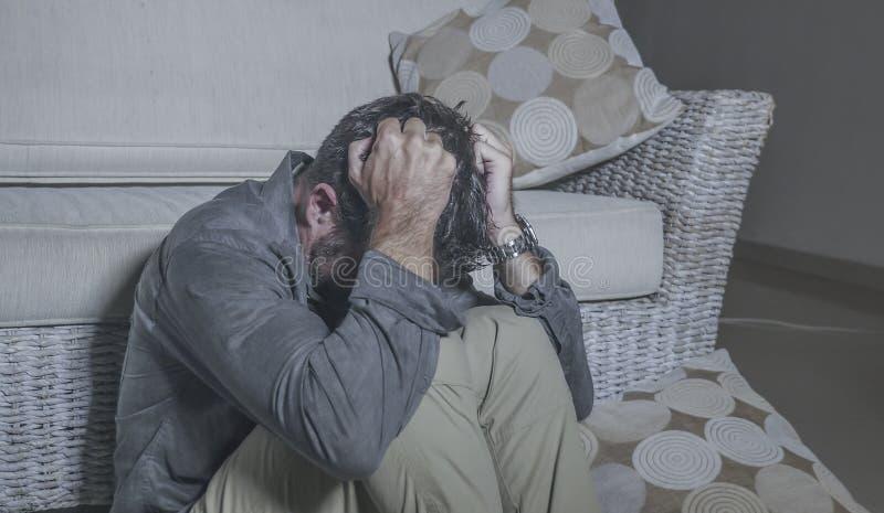 生活方式画象年轻可爱的哀伤和沮丧的人坐感觉客厅的地板绝望和被注重的痛苦 免版税库存图片