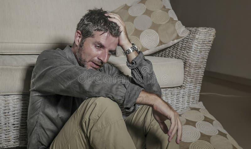 生活方式画象年轻可爱的哀伤和沮丧的人坐感觉客厅的地板绝望和被注重的痛苦 库存图片