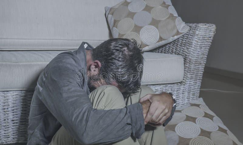 生活方式画象年轻可爱的哀伤和沮丧的人坐感觉客厅的地板绝望和被注重的痛苦 免版税库存照片