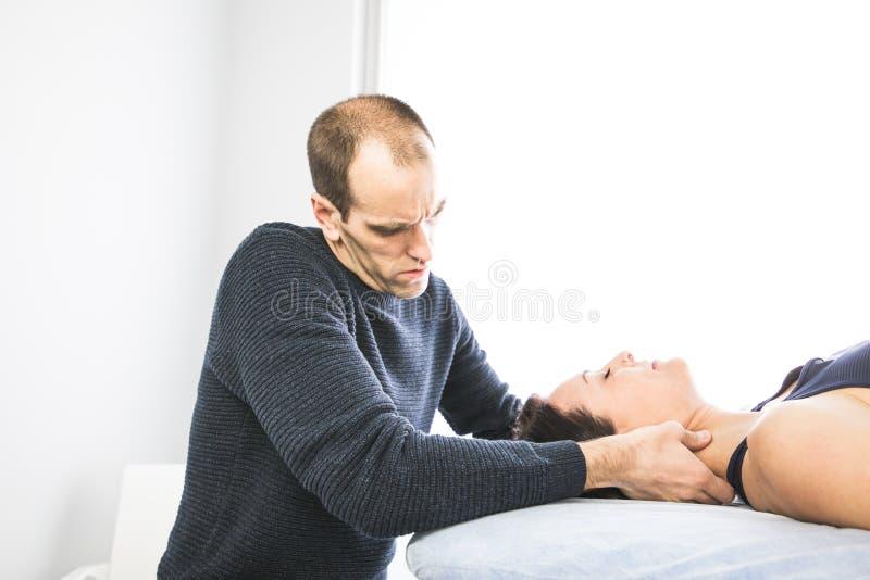 生理治疗师工作通过按摩脖子的一名患者 物理疗法的概念 免版税库存照片
