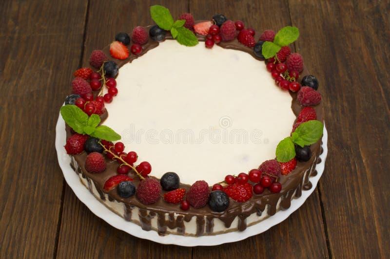 甜蛋糕用在木背景的新鲜的莓果 顶视图 免版税库存照片