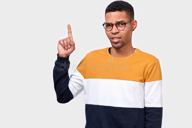 聪明的年轻人表明与前面手指在空白的拷贝空间,穿五颜六色的毛线衣,有正面微笑 免版税库存图片