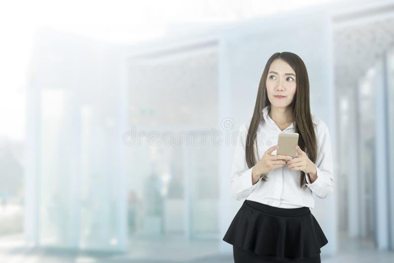 聊天由手机的年轻亚裔女商人 看拷贝空间 免版税库存照片