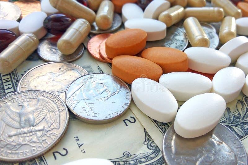 药片、片剂和胶囊与美国硬币在美元美国背景 免版税库存图片