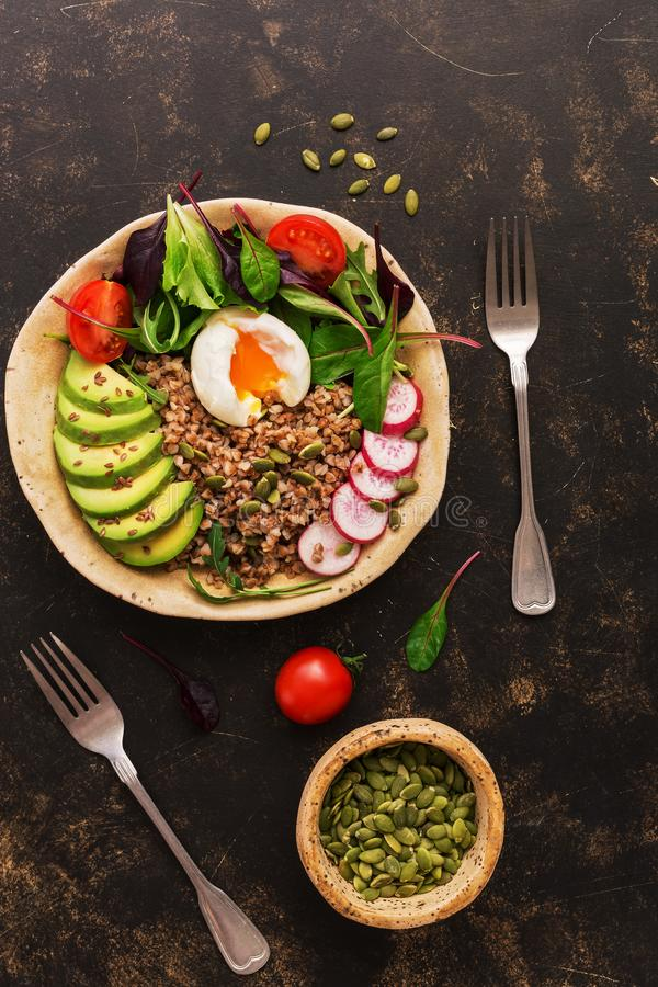 荞麦粥用熟蛋、鲕梨、萝卜、唐莴苣叶子、芝麻菜、蕃茄和种子 有健康食品的菩萨碗 顶层 图库摄影