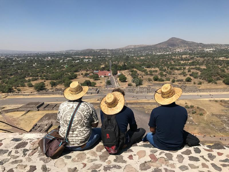 草帽的三个墨西哥男性游人坐与他们的后面对照相机在金字塔顶部反对mountai背景  免版税图库摄影