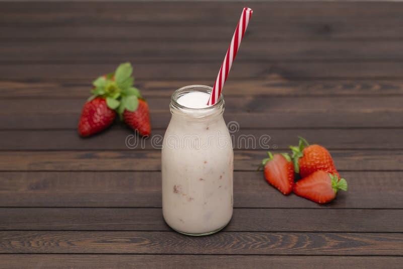 草莓圆滑的人或奶昔在玻璃瓶子有秸杆的用新鲜的莓果在木背景 库存照片